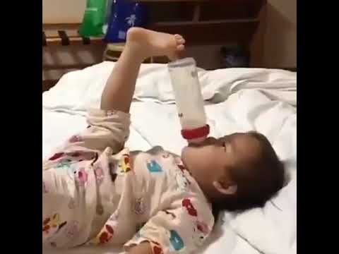 Cute and Funny Baby Holding The Baby Bottle With Its Foot ...