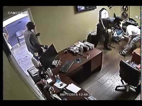 Surveillance video of auto parts store owner fighting back against two gunmen