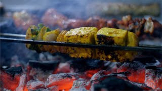 Seekh kebab and panner tikka being cooked over a furnace on a high flame