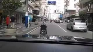 Cadeirante anda no meio da pista de rolamento na Avenida Brasil