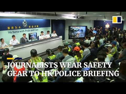 Journalists wear safety gear to Hong Kong police briefing