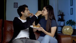Cute Indian couple in love feeding muffins to each other on valentine's day in India