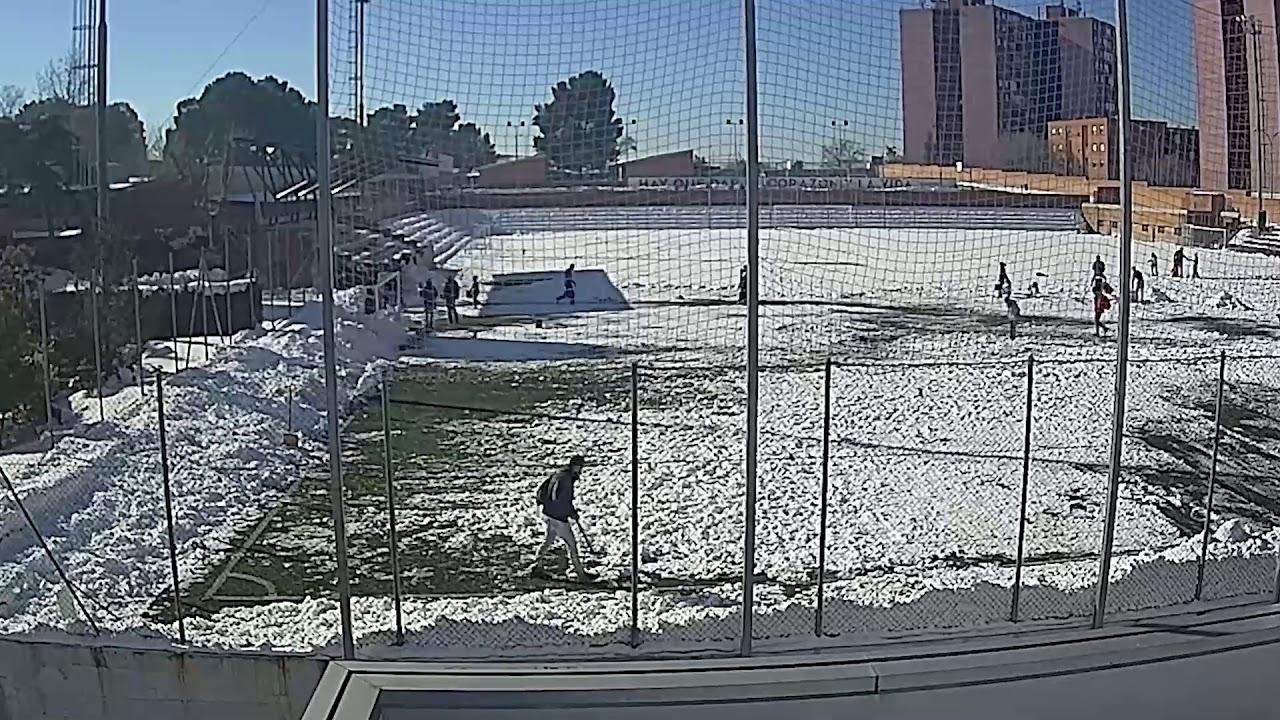 Familias retiran la nieve del campo de fútbol del colegio