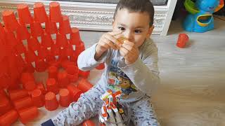 little boy playing with colored goblets