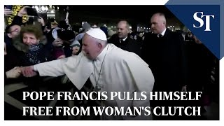 Pope Francis pulls himself free from woman's clutch