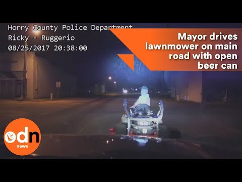 Mayor drives lawnmower on main road with open beer can