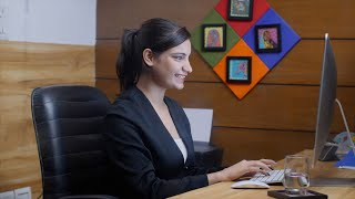 Young Indian entrepreneur very happy and rejoices sitting in front of desktop