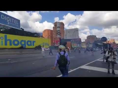 Venezuela: Protesters throw tear gas canisters back towards riot police in Caracas
