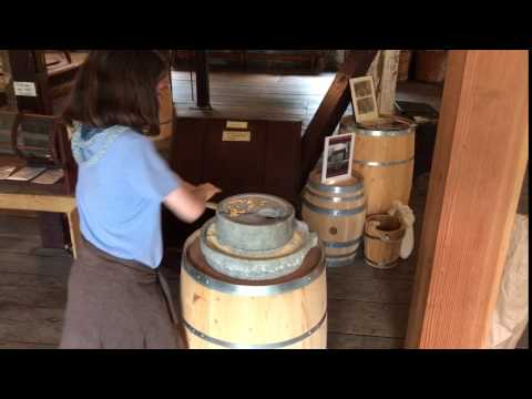 Peirce Mill visitor using quern stones to grind corn
