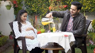Caring husband pouring fruit juice for his pregnant wife and himself on a date