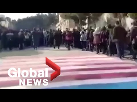 Iranian students avoid stepping on images of U.S., Israeli flags