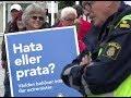 Socialdemokraten Marie Dahlin visar sitt hat och viftar polis i ansiktet