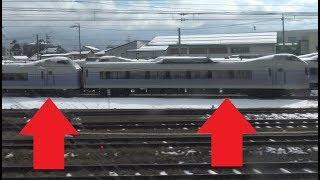 解体される元中央線特急スーパーあずさE351系の車両が並ぶ長野総合車両センター脇を通過する飯山線キハ110系の車窓
