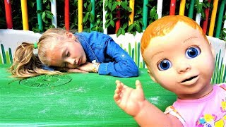 Polina plays hide and seek with baby doll on the playground