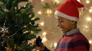 Happy little boy decorating and playing with the Christmas tree