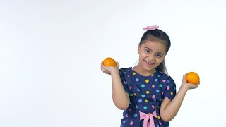 Pretty Indian girl having fun while playing with fresh oranges against the white background