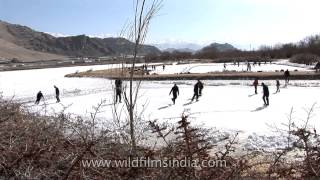 Boys ice skate on a frozen pond in the Indian Himalaya