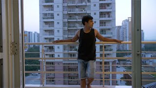 Shot of young Indian man / boy standing alone in his home balcony