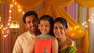 Nuclear Indian family portrait : Little daughter lighting diyas. Complete Family in India
