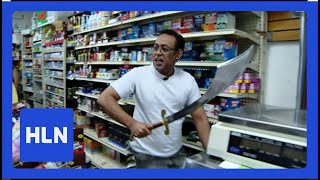 Robber pulls out machete; Clerk pulls out sword