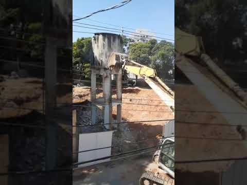 Caixa d'água de antiga delegacia é derrubada por trator