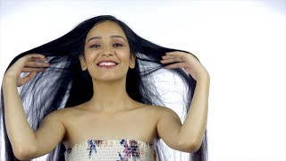 Smiling girl playing with her beautiful straight hair - hair and beauty concept
