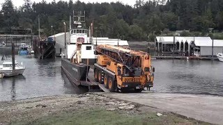 Giant truck crane drives onto small landing craft