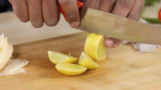 Closeup shot of a man slicing lemon into pieces on a wooden chopping board