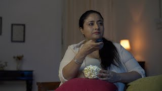Chubby Indian woman spending her bored and leisure time in watching television and eating popcorn