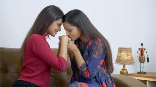 Indian lesbian couple sitting closely hand in hand and romancing each other