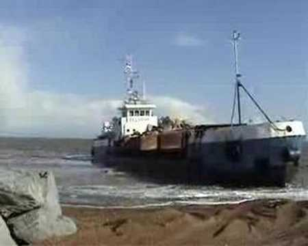 Timelapse of a ship dumping rocks on beach