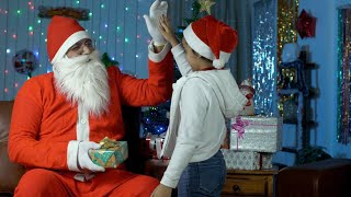 Cute little kid giving a colorful gift box to old Santa Claus during Christmas time