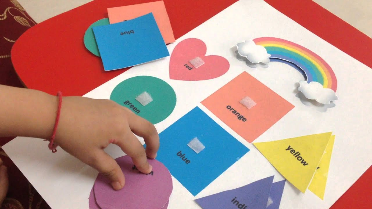 Toddler doing a rainbow-themed color & shape matching activity ...