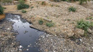Tilt shot of toxic water flowing in a garbage dump in India - bad ecology concept