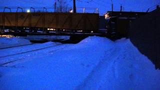 Снегоуборочная машина чистит рельсы на переезде.