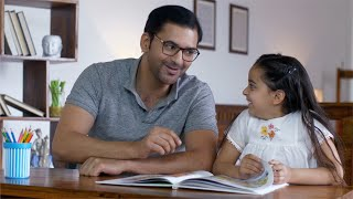 Indian father wearing spectacles reading story book with daughter