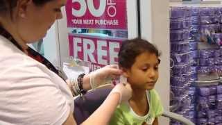 Julia getting her ears pierced at Claire s in the mall 05/26/2013