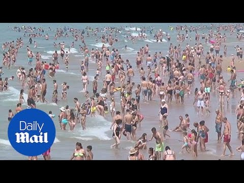 People invade beaches in Lisbon as heatwave hits Europe - Daily Mail