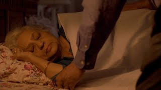 Footage of a old woman sleeping on bed, husband puts a blanket on her and turns off the light
