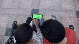 Young college couple using a green mock-up screen smartphone in landscape mode