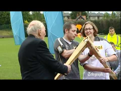 Sir Roger Bannister carries the London 2012 Olympic torch on the track of his triumph