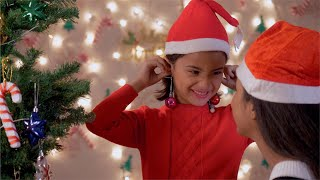 Cute little girl playing and making earrings out of Christmas decoration balls