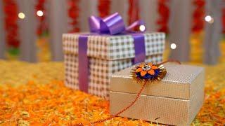 Tilt shot of a designer rakhi and a wrapped gift box for Raksha Bandhan Celebrations