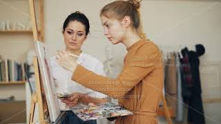 Charming art student girl is painting in studio under guidance of experienced female teacher. Master