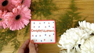Woman hands placing a 'congratulations' wish card on a decorated wooden table
