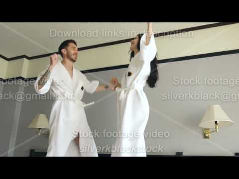 Slow motion of young happy couple in bathrobe jump and dance on bed in hotel during their honeymoon