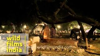Man lighting incense sticks at Nizamuddin graveyard - Shab-e-barat