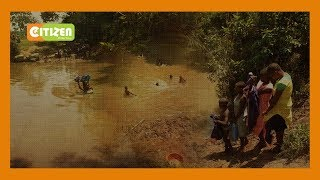 School children  who were swimming across River Lusumu benefit from a makeshift bridge