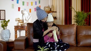 Young smiling mother teaching knitting to her little daughter at home - leisure concept