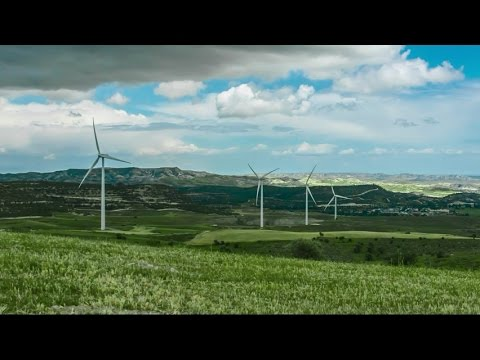 Beautiful green field with wind turbines rotating. Renewable energy source. Stock Footage